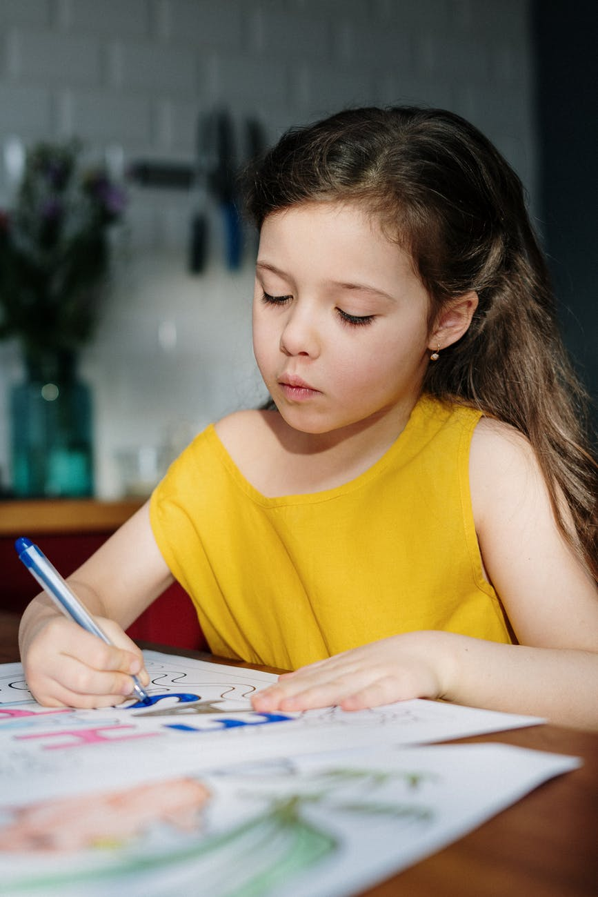 girl in yellow tank top writing on white paper