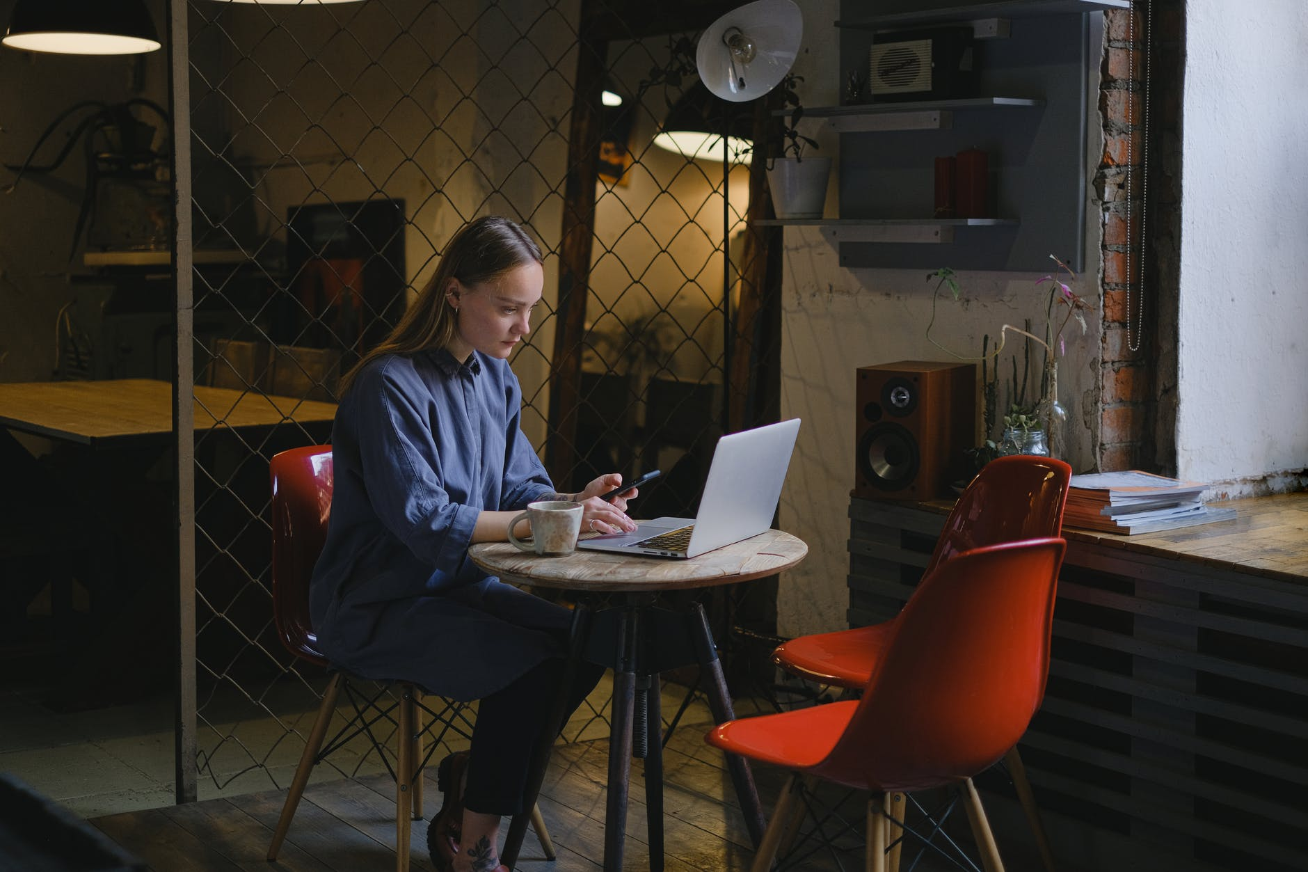 serious woman browsing laptop in cafe