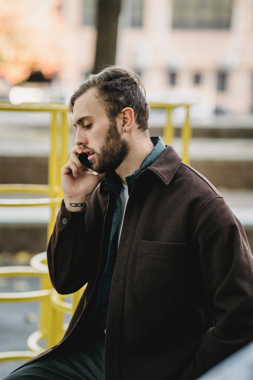 pensive man talking on smartphone on street