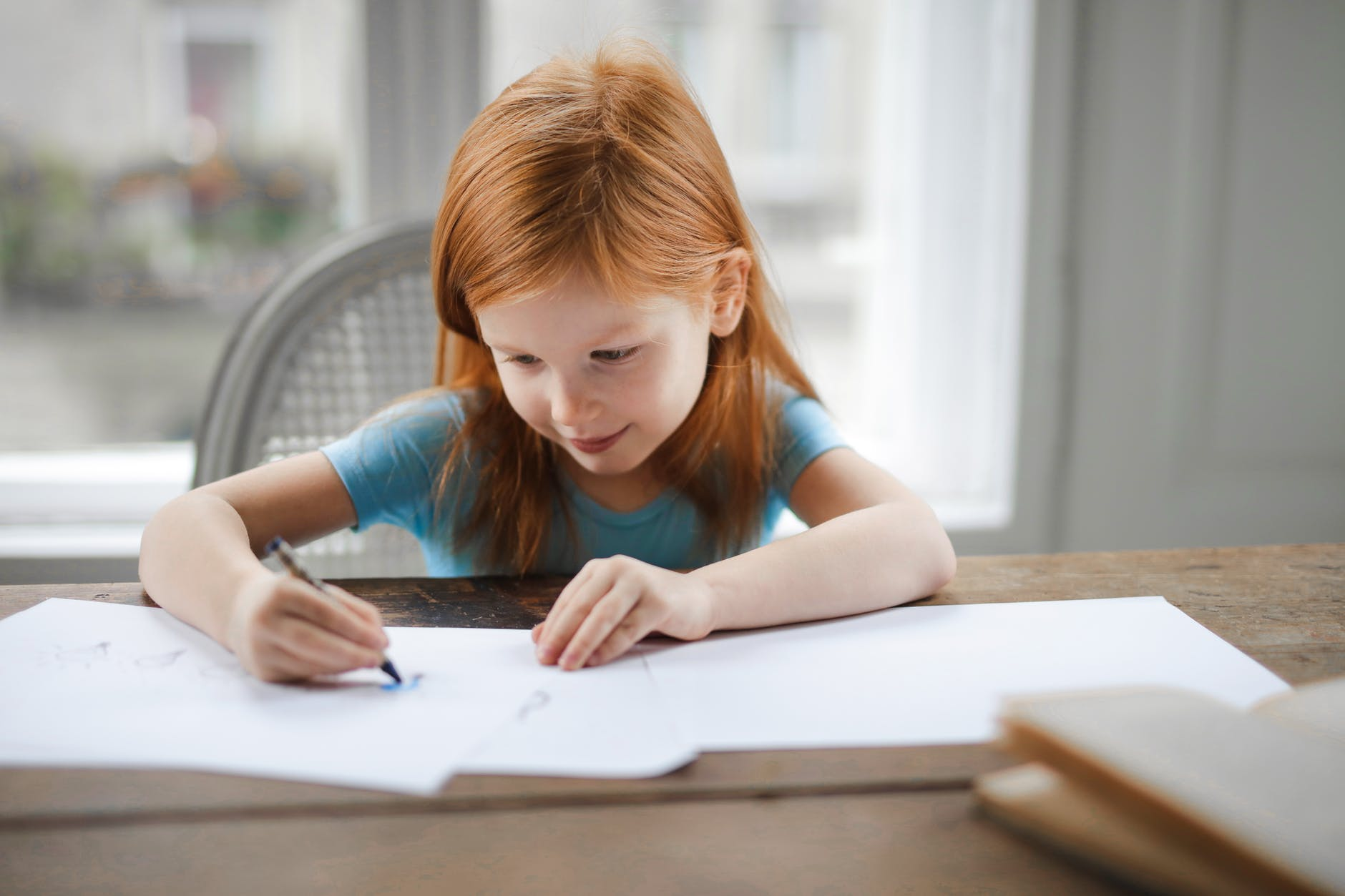 diligent small girl drawing on paper in light living room at home
