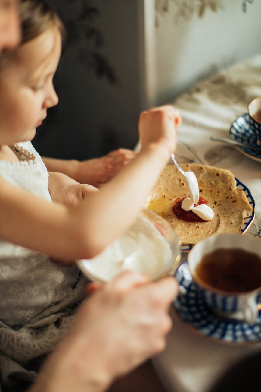 little cute girl spreading jam and cream on crepe