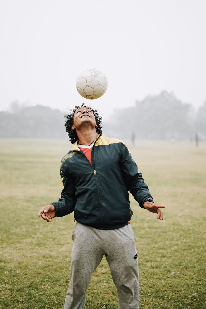adult happy sportsman hitting ball with head