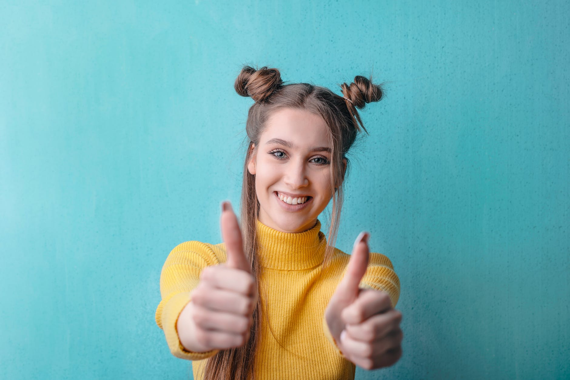 woman in yellow turtleneck sweater smiling