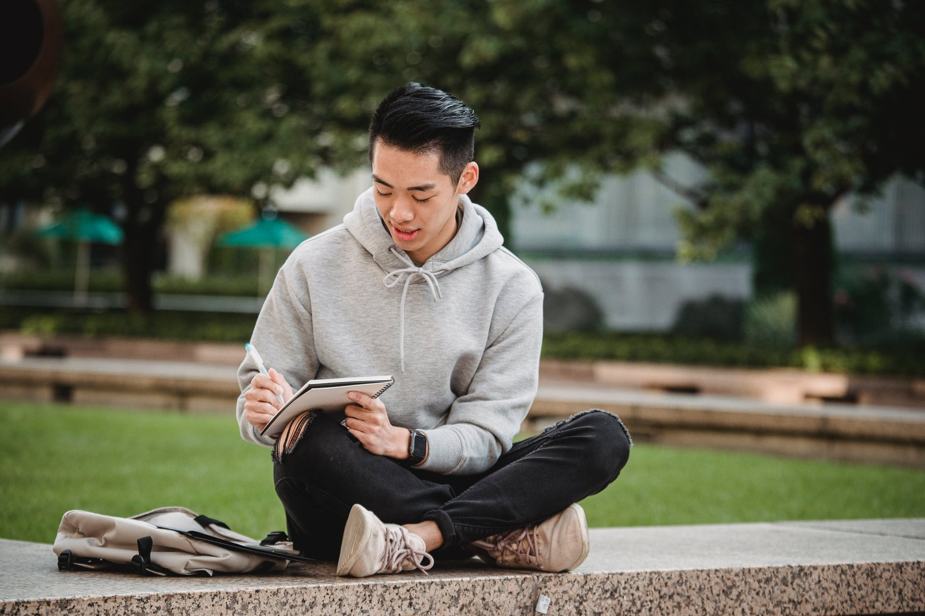 focused ethnic man with notebook and pen